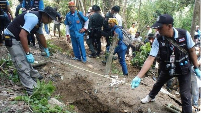 Thai police officials measure a shallow grave in Padang Besar, Songkhla province (2 May 2015)