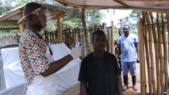 A man takes people's temperatures at the PTP refugee camp, in the south-eastern county of Grand Gedeh