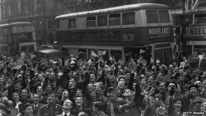Cheering crowds in Piccadilly Circus celebrate the German surrender on VE Day. (Photo by Keystone/Getty Images)