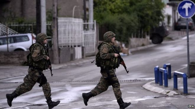 Police officers run across a street in Kumanovo, Macedonia, 9 May 2015.