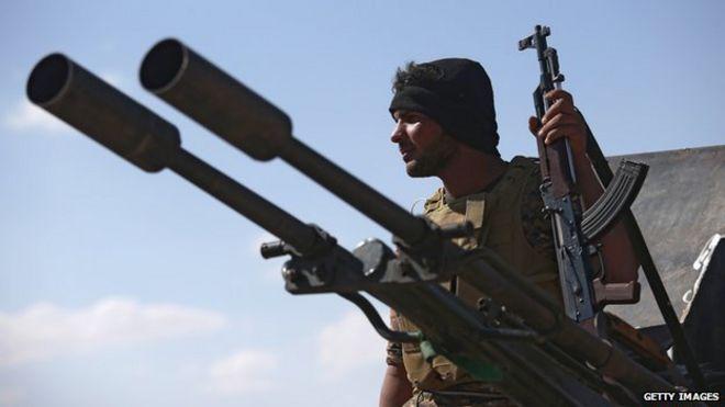 A Shia militiaman from Abu al Fadhel al Abbas watches as Iraqi Army troops attack IS fighters in Anbar Province, Iraq