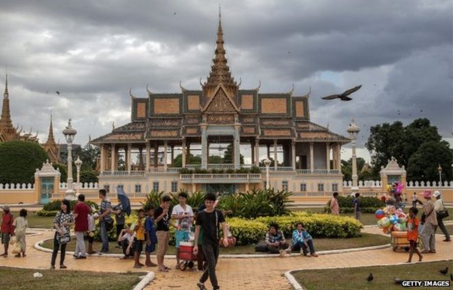 A group of Cambodian street vendors sells goods to tourists and local people in front of the Royal Palace