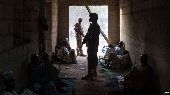 Nigerian soldier guarding civilians in Bama