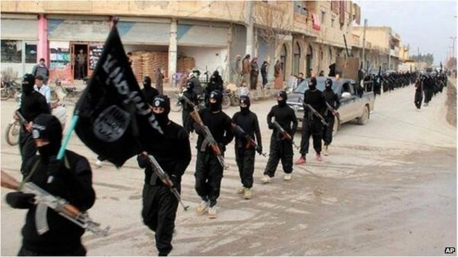 Armed and masked Islamic State militants marching with IS flag, Raqqa