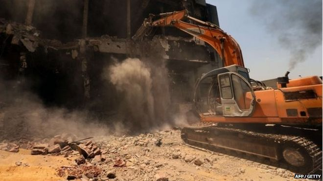 A bulldozer destroys the building of the headquarters of the once-dominant party of ex-president Hosni Mubarak that was torched during the 2011 uprising that toppled him on 31 May 2015 in Cairo.