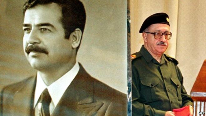 Tariq Aziz passes a poster of Saddam Hussein after a press conference in Baghdad - 24 November 1999