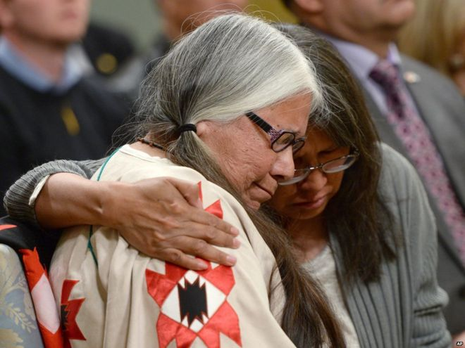 A woman is comforted in the audience during the closing ceremony of Commission