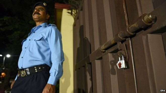A Pakistani security official stands guard at the Save the Children offices