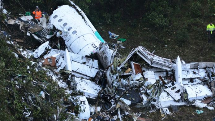 Rescue workers stand at the wreckage site of a chartered airplane that crashed in a mountainous area outside Medellin, Colombia, Tuesday, Nov. 29, 2016