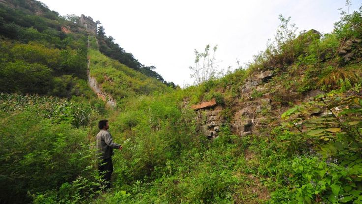 A villager look at the old brickwork of the Great Wall