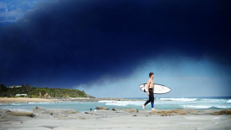 A surfer walks along a beach as smoke from the Wye River bushfire hangs overhead