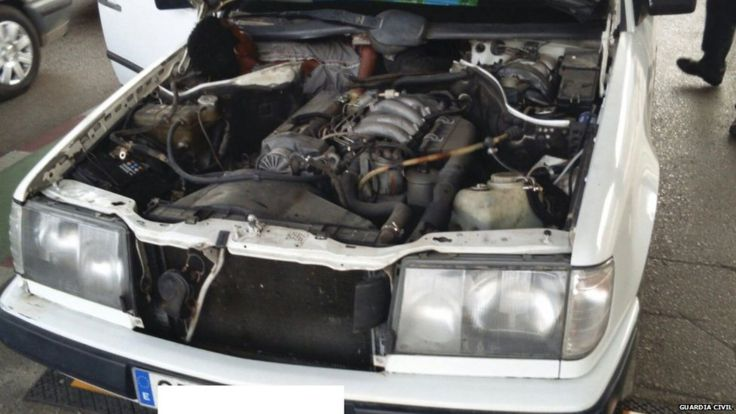 Guinea migrant next to car engine - Guardia Civil pic