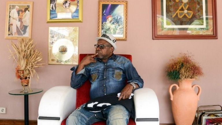 Papa Wemba posing in Kinshasa with some of his gold discs