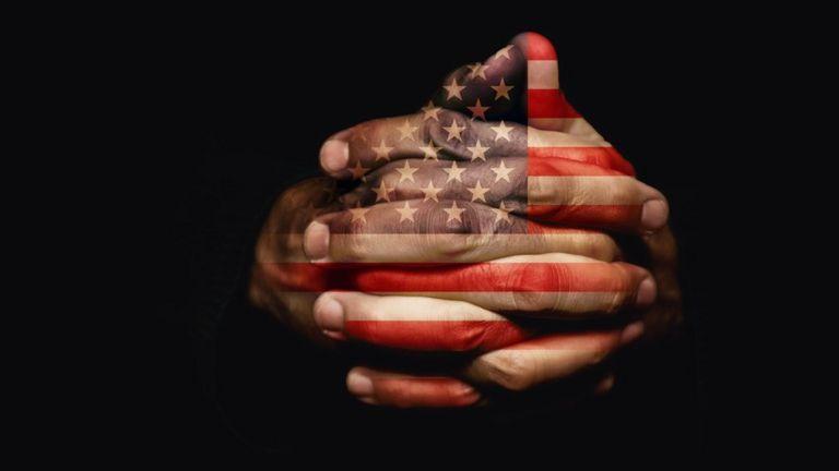 Manos con dedos entrelazados con la bandera de EE.UU. reflejada