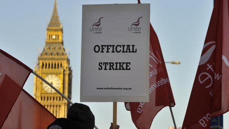 "A worker on strike holds a placard saying ""Official strike"", with Big Ben visible in the background"