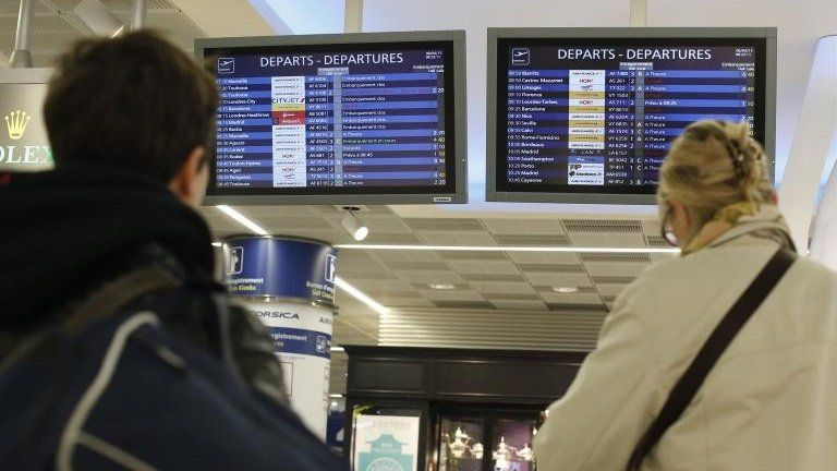 Passengers looking at departure boards at Orly airport