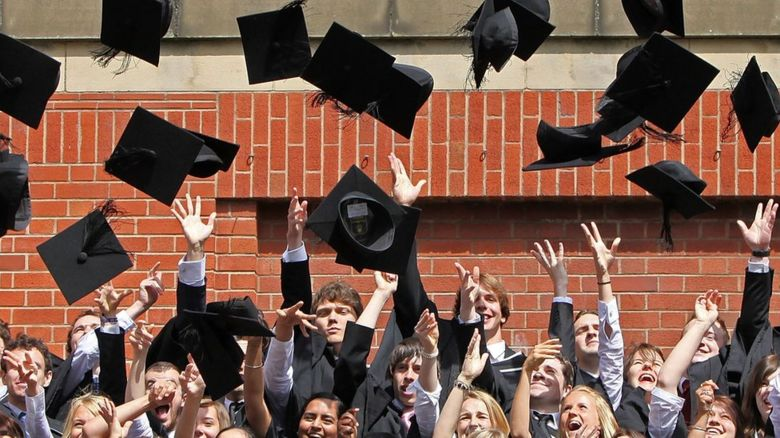 students throw their mortarboards in the air