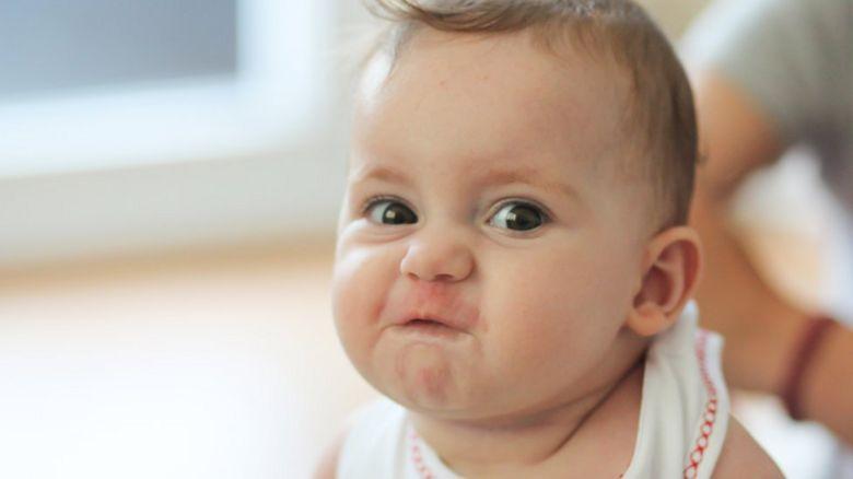 Baby pulling face at camera