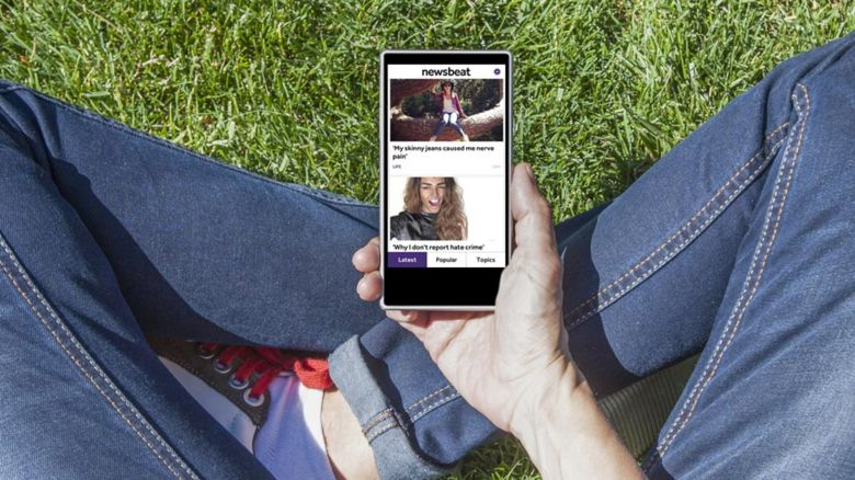 Newsbeat app being viewed by a person in skinny jeans in the park