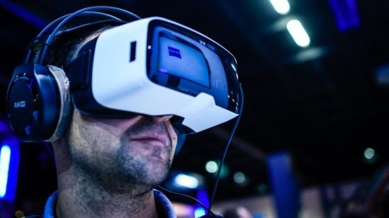 A visitor wears a virtual reality glasses and a pair of headphones play video games at the Gamescom 2015