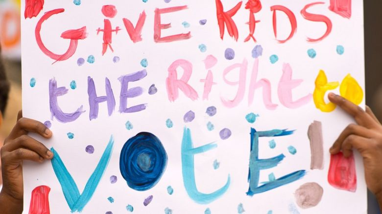 A placard saying %22give kids the right to vote%22