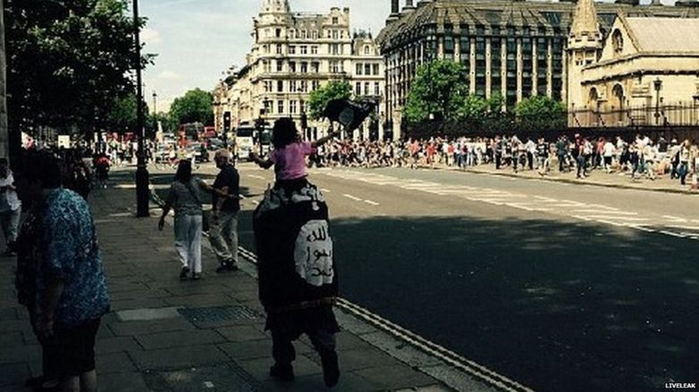 A man walks past the Houses of Parliament draped in what appears to be flag used by so-called Islamic State with a young child on his shoulders