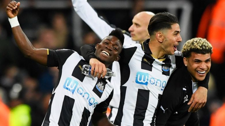 Christian Atsu, Ayoze Perez and DeAndre Yedlin of Newcastle United celebrate victory and promotion