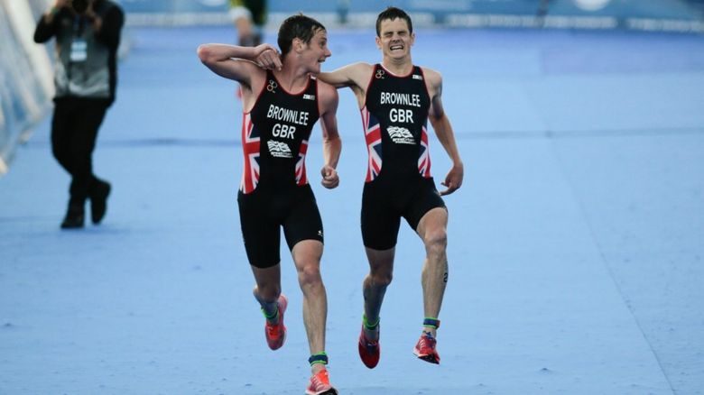 Alistair Brownlee helps his brother Jonathan towards the finish line