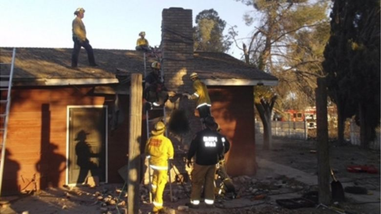 Firefighters trying to take apart the chimney