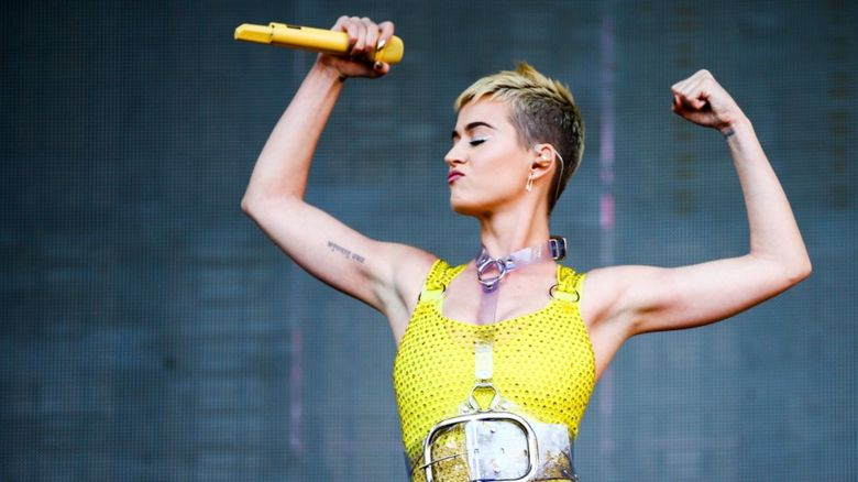 This is a photo of singer Katy Perry performing and flexing her muscles.