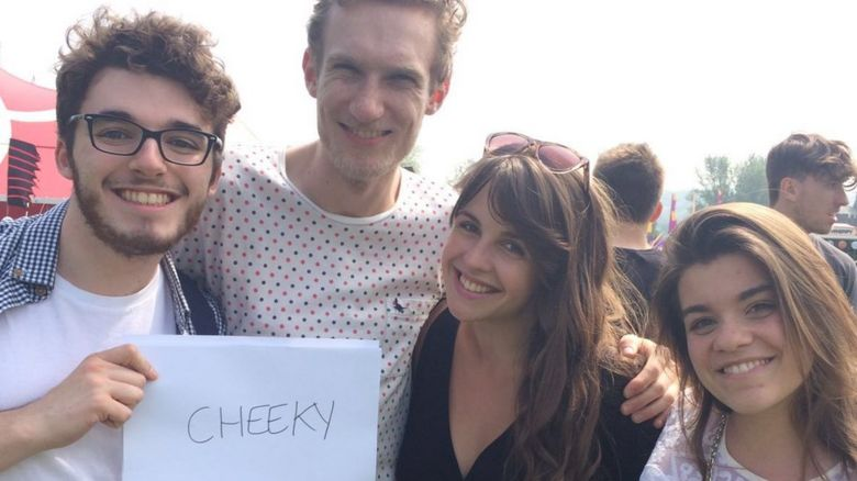 People holding a sign saying cheeky