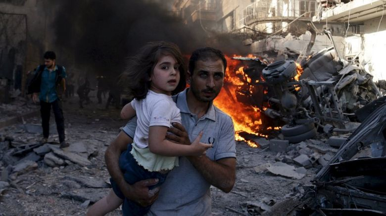 A man carries a girl as they rush away from a site hit by what activists said were airstrikes by forces loyal to Syria%22s President Bashar al-Assad in the Douma neighbourhood of Damascus,