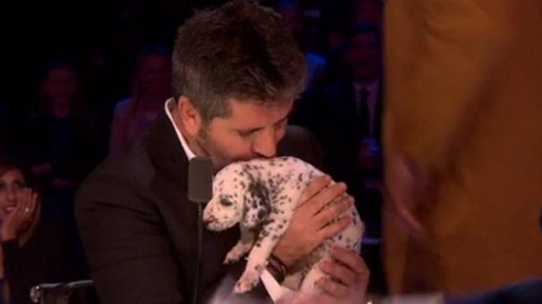 Simon Cowell kissing a puppy