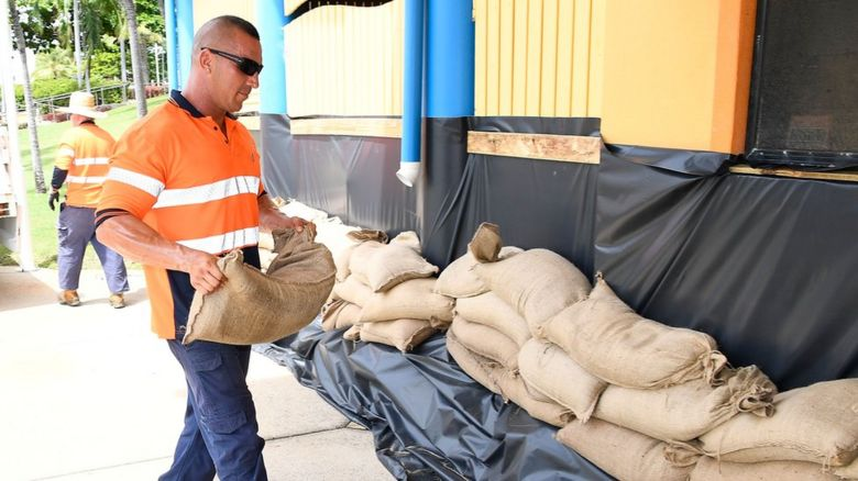 A man piling sandbags to help protect buildings from the storm