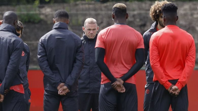 The Manchester United squad holds a minute's silence after Monday's attack