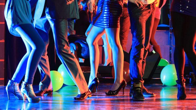 Men and women's legs on a dancefloor