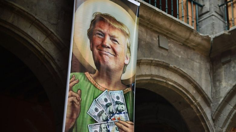 A poster of Donald Trump holding lots of bank notes
