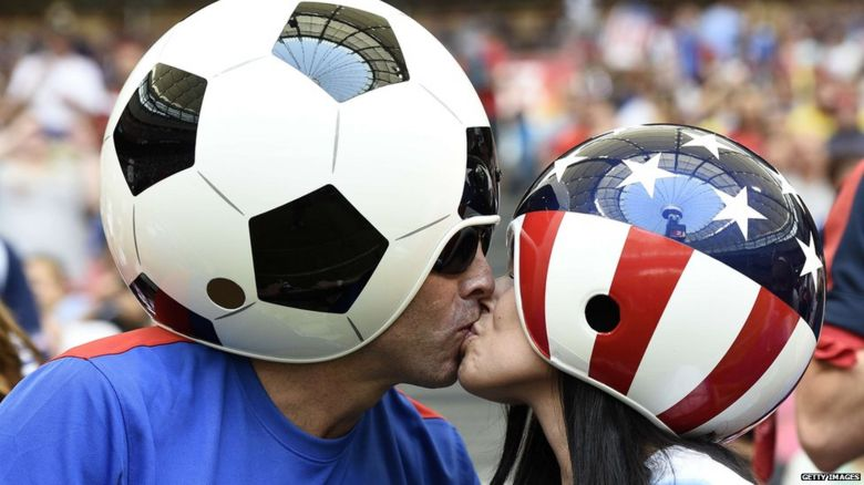 US football fans kiss in football and American flag helmets