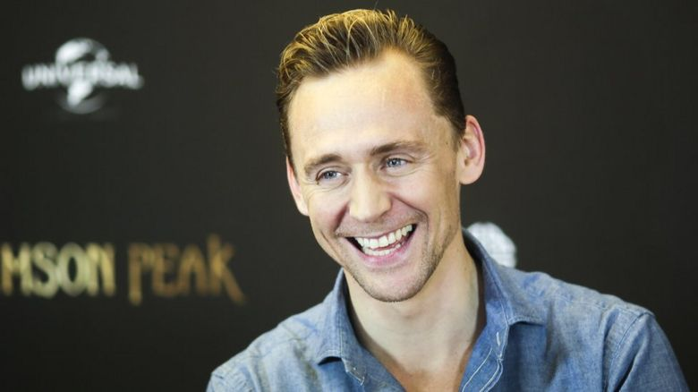 Tom Hiddleston happily grins for the cameras promoting his current film, a gothic horror called Crimson Peak