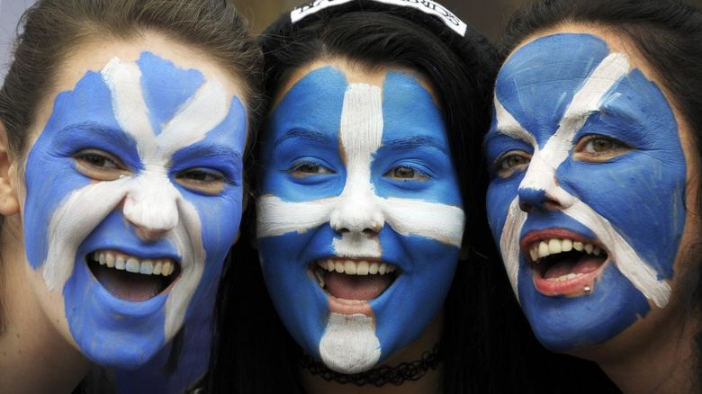 Three girls with the Scottish flag face painted on them