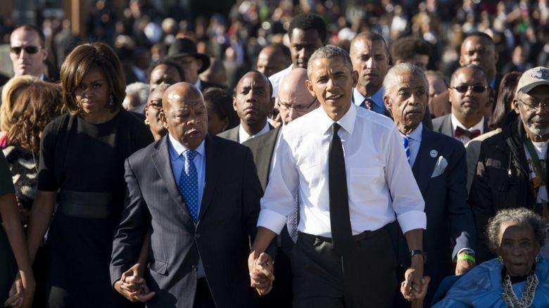 John Lewis hand in hand with Barack and Michelle Obama on the 50th Anniversary of the Selma to Montgomery civil rights march in 2015
