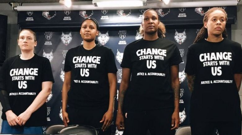 "Maya Moore, Seimone Augustus, Lindsay Whalen, and Rebekkah Brunson wearing black shirts with the phrase ""Change Starts With Us: Justice & Accountability."""