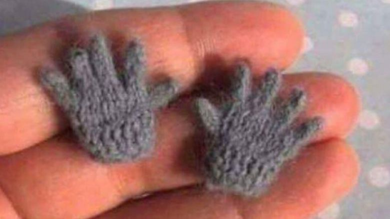 Hand holding small gloves