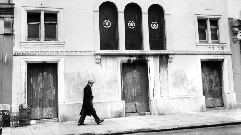 Man walking in front of a synagogue