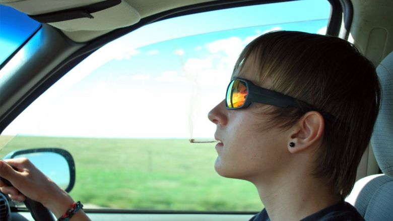 Young driver smoking at the wheel