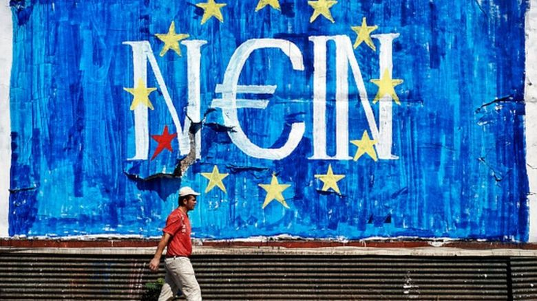 A man walks past anti-EU graffiti in Athens, Greece