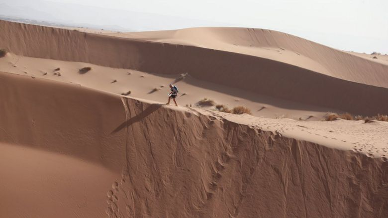 A man walking across a sand dune