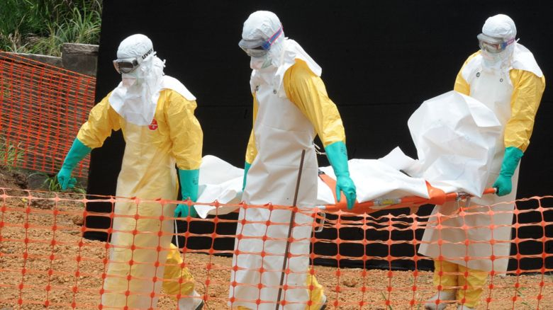 Doctors in protective suits carry the body of a person who died from the Ebola virus