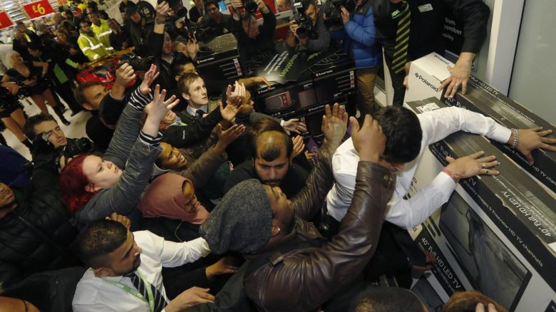 People in a shop pushing to get to televisions