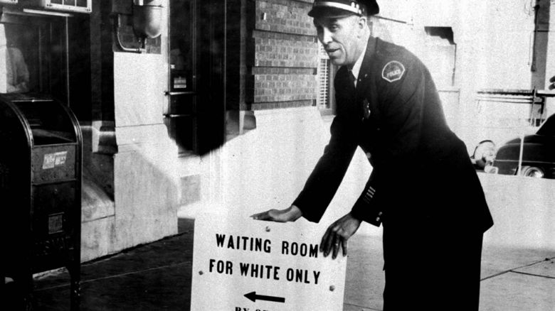 Policeman with a sign reading: %22Waiting room for white only by order police dept.%22